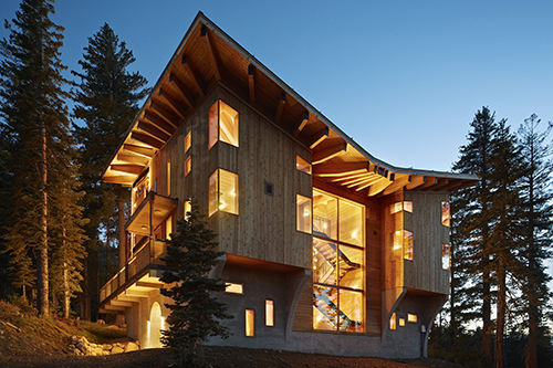 Contemporary wood mountain home lit up at night - Jumbo Loans