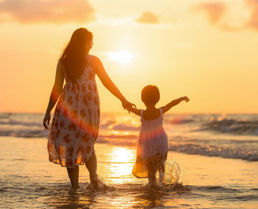 mom and child on beach at sunset with ocean - conventional loans
